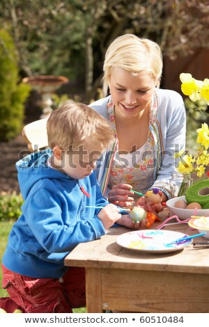 Mother And Son Decorating Easter Eggs On Table Outdoors Stock photo © monkey_business