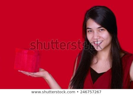 Beautiful biracial teen girl in red dress holding red present on Stock photo © jarenwicklund