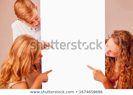 young girl pointing towards copy space area stock photo © stockyimages