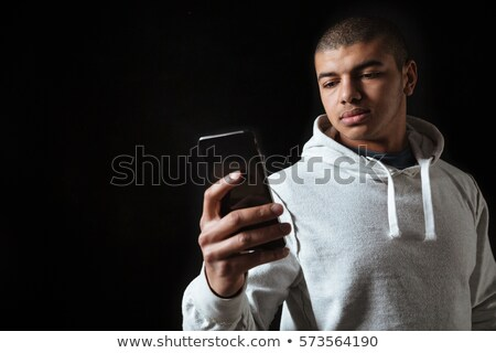 serious african man in hoodie standing and using cell phone stock photo © deandrobot