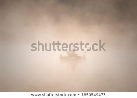 Sylwetka rybaka łodzi rzeki wygaśnięcia górę Zdjęcia stock © vlad_star