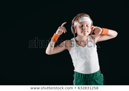portrait of sportive boy listening music in headphones isolated on black Stock photo © LightFieldStudios