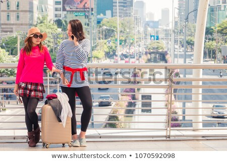 Portrait of two pretty young girls standing on a city street Stock photo © deandrobot