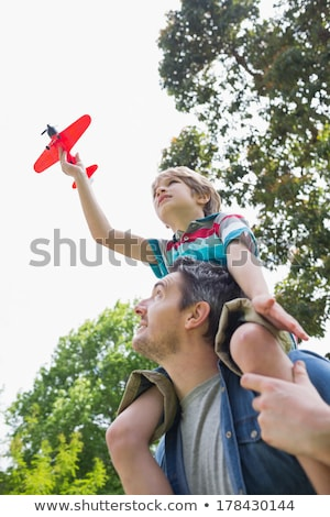 Stock photo: Low angle view of a boy with toy aeroplane sitting on fathers shoulders at the park