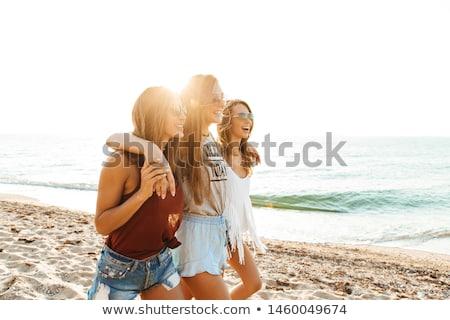 Three hugging girls at the beach. stock photo © Massonforstock
