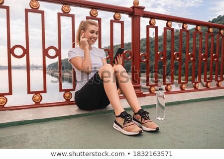 Young pretty sports woman preparing to run while using smartphone Stock photo © deandrobot