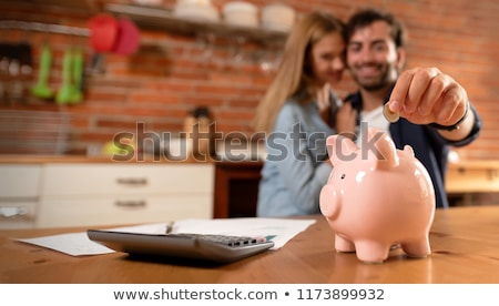 Man Inserting Coin In Piggybank Stock photo © AndreyPopov