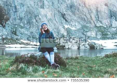 Amazing young beautiful woman sitting outdoors using laptop computer. Stock photo © deandrobot