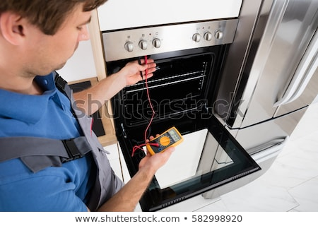 Male Technician Repairing Oven Stock photo © AndreyPopov