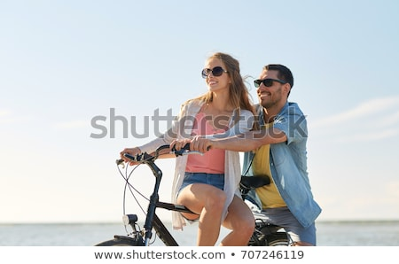 happy young couple riding bicycles at seaside stock photo © dolgachov
