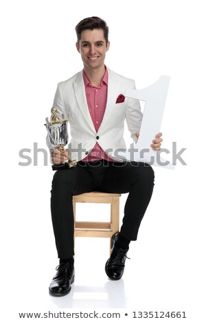 smiling elegant champion sitting and holding his prizes Stock photo © feedough