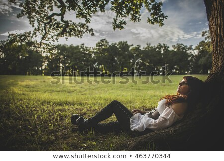 Foto stock: Young Brunette Woman Is Laying In The Grass Looking Up