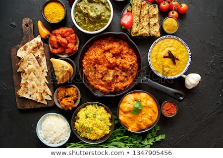 Various Indian dishes on a table. Spicy chicken Tikka Masala in iron pan Stock photo © dash