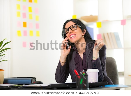 Cheerful young businesswoman sitting at her workplace Stock photo © deandrobot