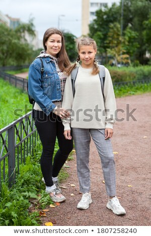 Full length of two happy young students girls standing outdoors Stock photo © deandrobot