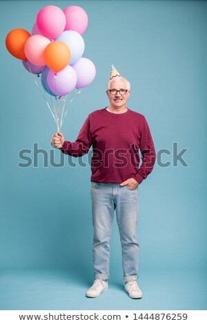 Happy mature man in birthday cap and casualwear holding balloons Stock photo © pressmaster