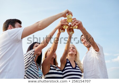 happy friends drinking non alcoholic beer on beach stock photo © dolgachov