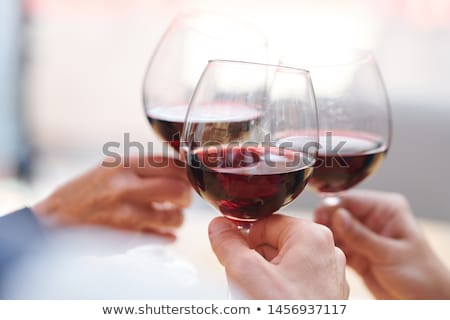 Three wineglasses with red cabernet held by toasting friends Stock photo © pressmaster