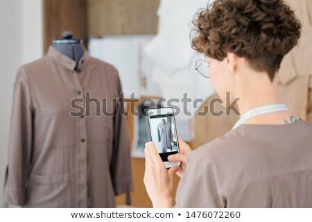 Fiatal női szabó okostelefon fényképezés kabát Stock fotó © pressmaster