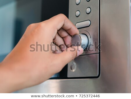 Woman Pressing Button Of Microwave Oven Stock photo © AndreyPopov