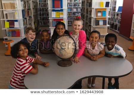 Front view of happy schoolkids with globe looking at camera in school library Stock photo © wavebreak_media