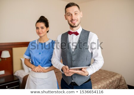 Young successful porter and pretty chamber maid in uniform Stock photo © pressmaster