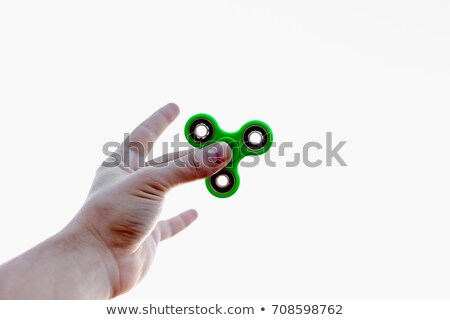 Close up of a man's hand who is holding a fidget spinner in a park Stock photo © galitskaya