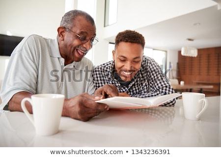 Mosolyog idős férfi néz fényképalbum boldog Stock fotó © HighwayStarz