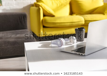 Image of furnished room with coffee cup, headphones and laptop o Stock photo © deandrobot