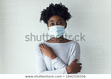 Serious Afro American woman wears disposable medical mask on face, being on self isolation during qu Stock photo © vkstudio