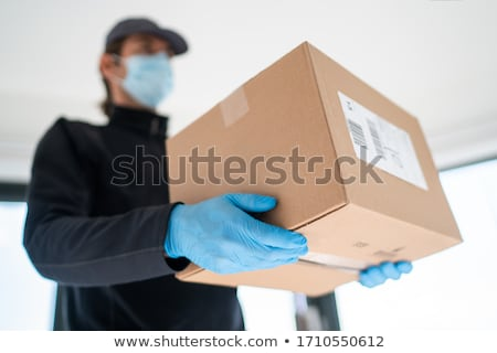 Home delivery shopping box man wearing gloves and protective mask delivering packages at door Stock photo © Maridav