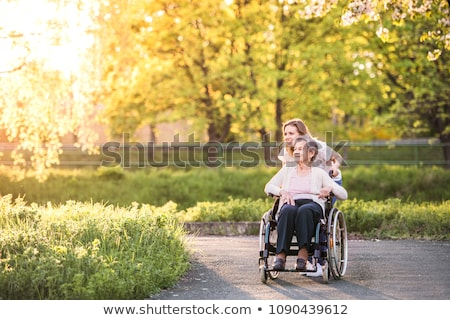 Young woman pushing an elderly woman in a wheelchair Stock photo © photography33