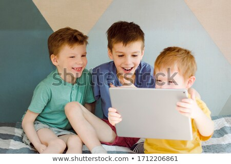 Laughing baby looking at a tablet computer indoors stock photo © wavebreak_media