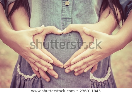 hands of pregnant woman and her husband in heart shape stock photo © dacasdo