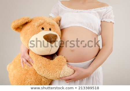 Pregnant woman hugging her belly and a teddy bear Stock photo © photography33
