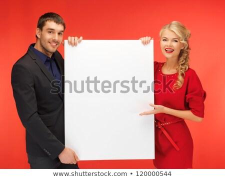 elegant couple holding the empty board stock photo © konradbak