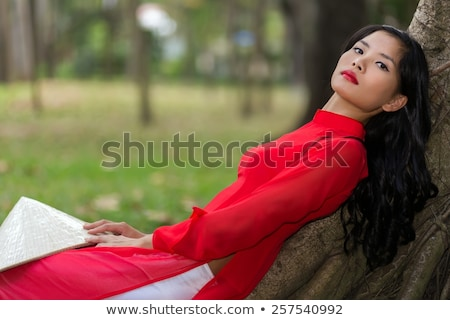 Slender young Vietnamese woman relaxing in a park Stock photo © smithore