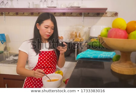 Young woman Following Recipe On mobile phone Stock photo © Witthaya