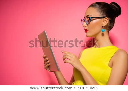 smiling woman in a dress holding a tablet computer stock photo © juniart