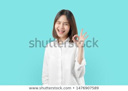 A pretty girl with brace show a sign O.K. Stock photo © digoarpi
