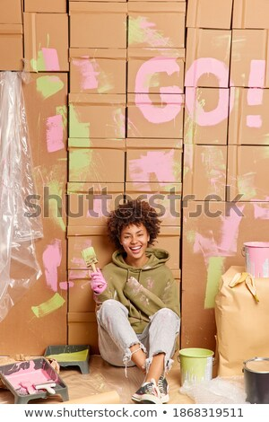 Woman dirty with paints sitting and holding paintbrush Stock photo © deandrobot