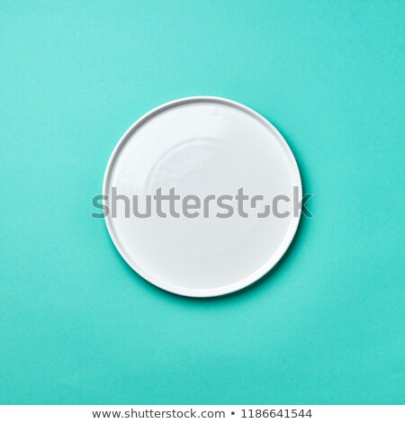 Decorative ceramic empty white handmade plate presented on a gray concrete background with copy spac Stock photo © artjazz