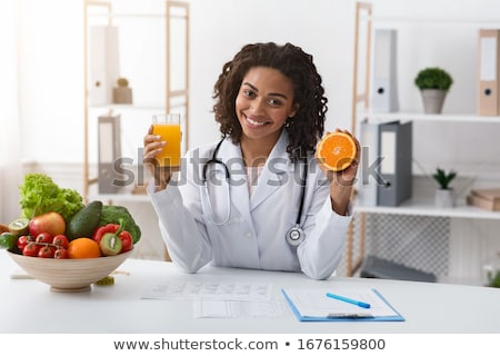 Female nutritionist hold oranges and glass of fresh juice in her hands isolated on white background Stock photo © Traimak