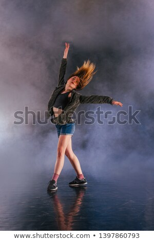 Flexible girl dancer holding a colorful flare Stock photo © konradbak