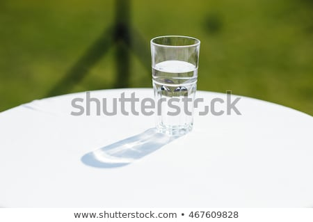 Glass of water lightened with sun on a white table Stock photo © ruslanshramko