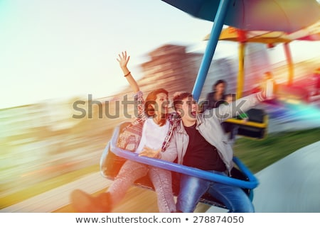 Beautiful, young man having fun at an amusement park Stock photo © galitskaya