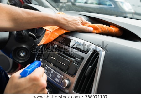 Man at work cleaning inside automobile at car wash Stock photo © Lopolo