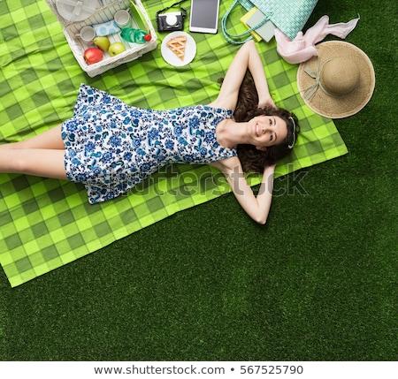 smiling teenage girls lying on picnic blanket Stock photo © dolgachov