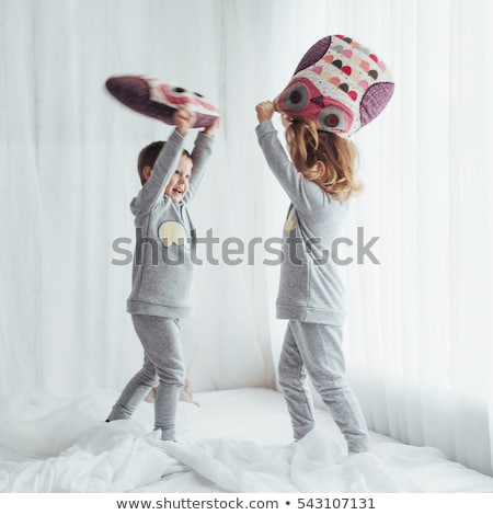 two girls playing pillow in bedroom stock photo © colematt