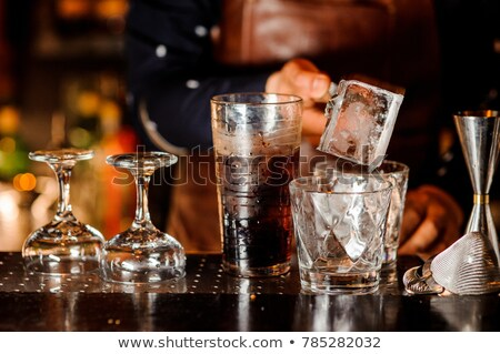 Bartender pouring ice cube in glass  Stock photo © grafvision